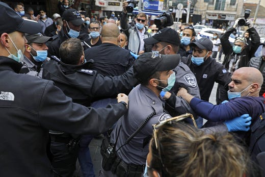 Israeli policemen wearing protective face masks, scuffle with merchants in Jerusalem's Mahane Yehuda market, on April 26, 2020, protesting against the continued closure of the landmark open air market, after authorities reduced some lockdown measures imposed in order to stem the spread of the novel coronavirus, by allowing shops to reopen.