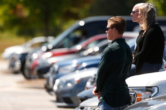 Members of the congregation watch from the hood of their car during an outdoor church service at Cornerstone Church in Athens, Ga., on April 26, 2020.