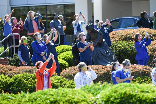 AnMed Health staff and bystanders take photos and video of F-16 planes from The South Carolina Air National Guard 169th Fighter Wing flying over the hospital in Anderson, S.C. Monday, April 27, 2020.