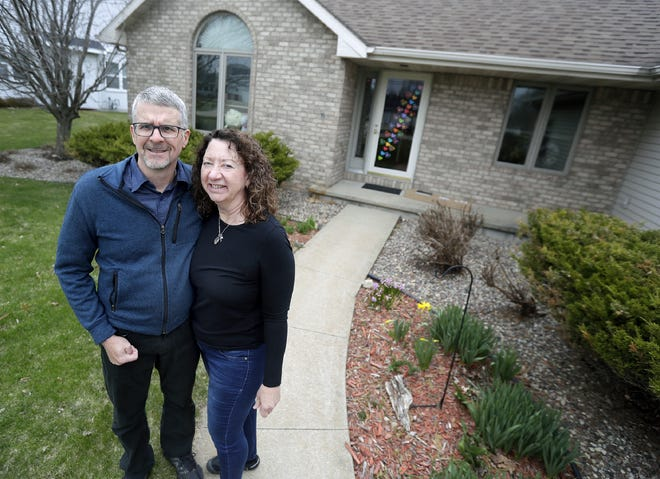 Gail and Steve Heuser stand outside their home on April 23, 2020 after returning from New Zealand.