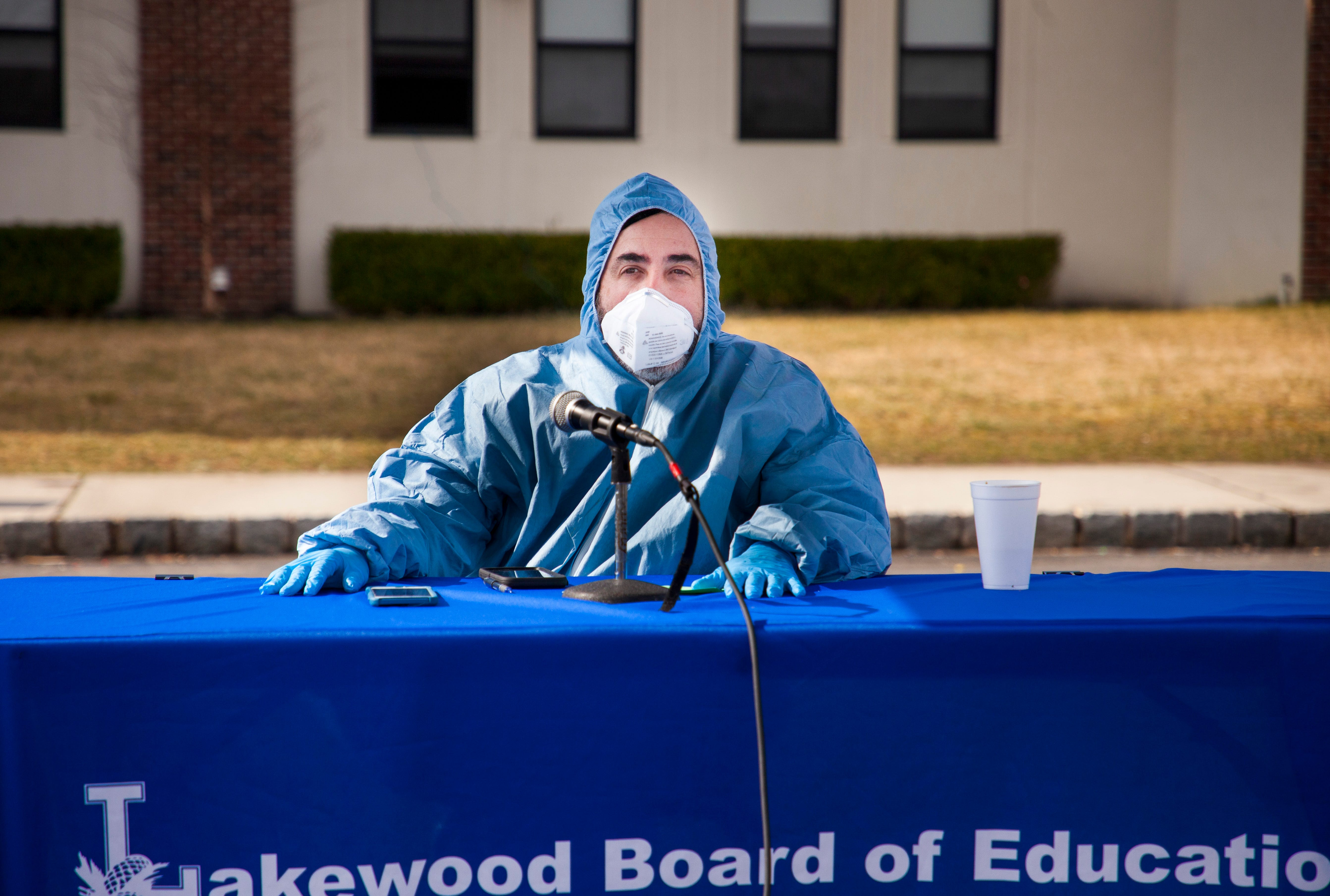In this March 20, 2020, photograph, Michael Inzelbuch, Lakewood Board of Education attorney and spokesperson, wears personal protective equipment during one of his daily updates from the parking lot of a non-public school. During the coronavirus pandemic, Inzelbuch streamed his daily updates online from different locations.