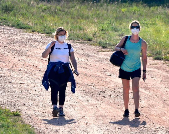 A pair of hikers walk down the road at Lake Abilene on Saturday.