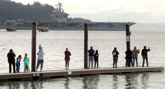 People line the dock in Manchester as the USS Nimitz exits Rich Passage on Monday, April 27, 2020.