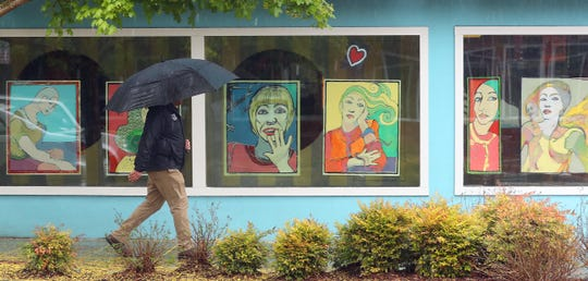 Portraits look on from the windows of the Amy Burnett Gallery building as a pedestrian with an umbrella strolls by on a rainy Wednesday, April 22, 2020, in downtown Bremerton.