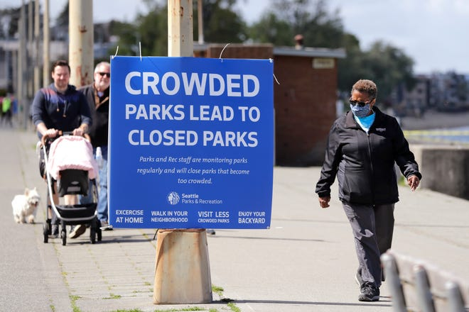 Velma Mullen, right, wears a protective mask as she walks past a sign advising park users to keep physical space between them Monday, April 27, 2020, in Seattle. City guidelines for Seattle parks ask that people stay at least six feet apart, not to congregate and to keep moving to help prevent spread of the coronavirus.