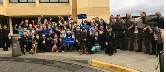 On Friday the Bremerton Police Department posted on social media this photo, then deleted it, showing officers gathered close with Harrison Medical Center employees.