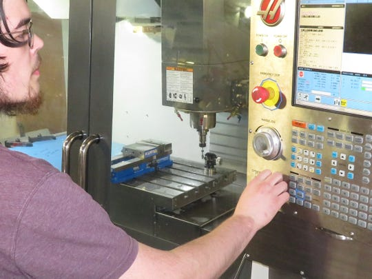 Tyler Dailey machining a ventilator part on a computerized milling machine.