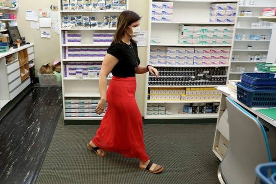 Pharmacist Christina Schreiner Spille, of Edgewood, Kentucky, walks to answer the phone as she takes orders and fills prescriptions, Monday, April 27, 2020, at Faith Community Pharmacy in Florence, Ky. Faith Community Pharmacy serves 14 counties in Kentucky that are in part of the Covington Diocese. St. Vincent de Paul Charitable Pharmacy in the Cincinnati area helps people in Hamilton, Butler, Warren and Clermont counties.