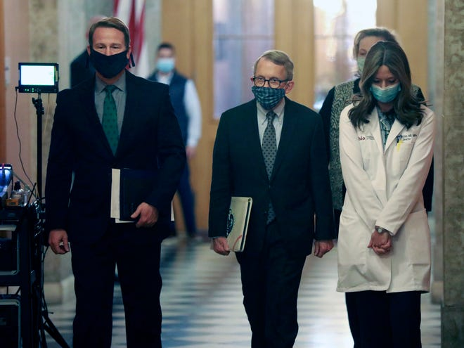 Wearing their protective masks, from left, Ohio Lt. Gov. Jon Husted, Gov. Mike DeWine, and Ohio Department of Health Director Dr. Amy Acton walk into their daily coronavirus news conference Wednesday, April 15, 2020 at the Ohio Statehouse in Columbus, Ohio.