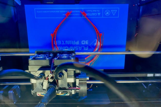 A 3D printer produces one of the first face shield frames made at the APSU GIS Center in Clarksville, Tennessee.