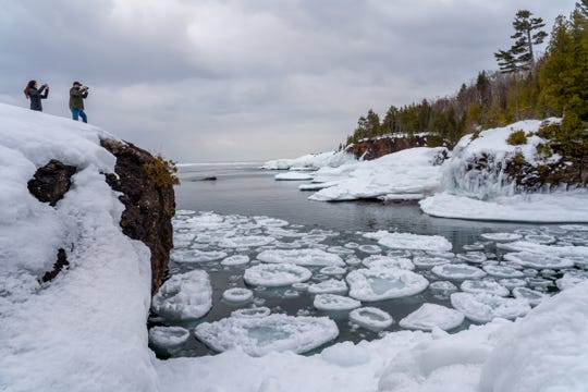 People take photos of the scene where pancake ice is formed on Lake Superior at Presque Isle Park in Marquette on Tuesday, March 3, 2020 in Michigan's Upper Peninsula.