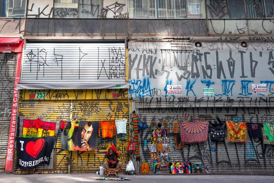 A street vendor sells his merchandise in front of shuttered stores on a sidewalk left empty due to a quarantine imposed by the state government to help contain the spread of the new coronavirus in Sao Paulo, Brazil, Monday, April 27, 2020.
