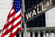 This Monday, July 15, 2013, file photo shows the American flag and Wall Street sign outside the New York Stock Exchange.  Stocks around the world rose Monday as governments prepare to gradually lift restrictions they imposed on businesses to slow the sweep of the coronavirus pandemic.