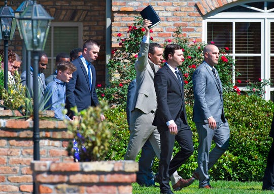 Pastor Tony Spell of Life Taberbacle Church in Central, La. leaves his residence behind the church Sunday, April 26, 2020, holding a Bible aloft while being escorted into the church for the service.