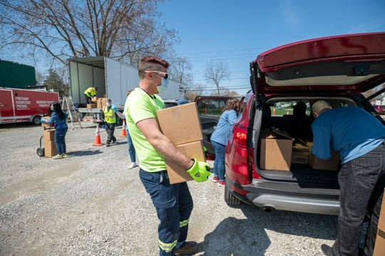 Matt Hertz, with Service Towing, helps Area Agency on Aging 1B staff load boxes of food into seniors' cars at a pop-up pantry in Warren, April 27, 2020.