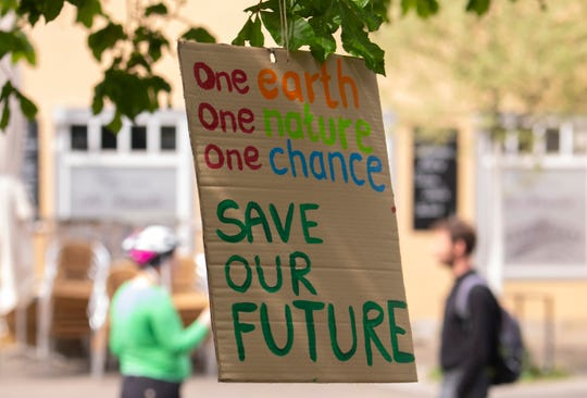 Activists of the fridays for future movement placed a poster at a tree in Erfurt, Germany, Friday, April 24, 2020. Youth groups are staging a long-planned global climate demonstration online because of restrictions on public protests during the coronavirus pandemic.