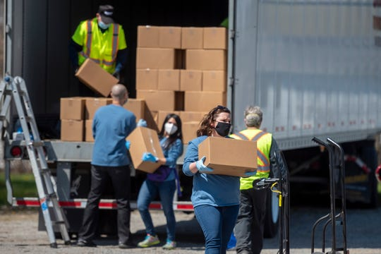 Area Agency on Aging 1B staff and volunteers load boxes of food into seniors' cars at a pop-up pantry in Warren, April 27, 2020.