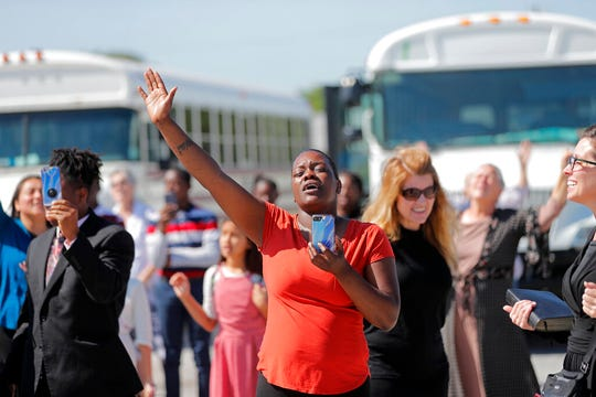 Members of the Life Tabernacle Church sing spiritual songs and hold their hands in the air as they wait for pastor Tony Spell to leave the East Baton Rouge Parish jail in Baton Rouge, La., Tuesday, April 21, 2020.