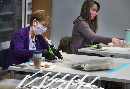 Janet Stephenson and Janine Kaznowski work on  protective face shields at Prefix, a small manufacturing company producing personal protective equipment in Auburn Hills, Michigan on April 27, 2020.