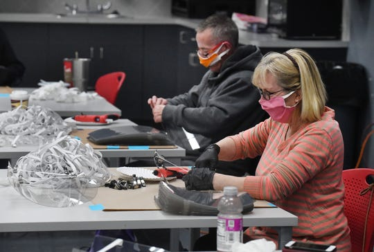 Carol Pennington and Robert Guilloz, in background, work on protective face shields at Prefix Corp., a Rochester Hills-based supplier of race engines that has transformed itself into make protective equipment for first responders, hospitals andother businesses.