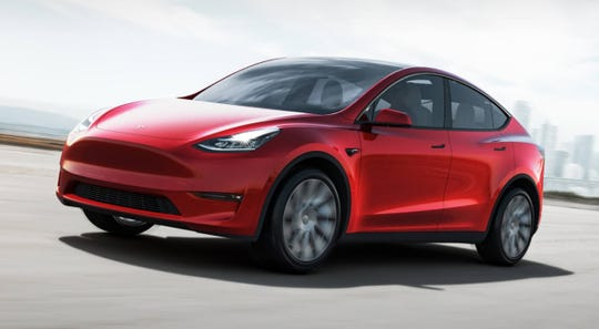 Tesla is rolling out a new feature of its partially automated driving system designed to spot stop signs and traffic signals. The Tesla Model Y crossover is shown.