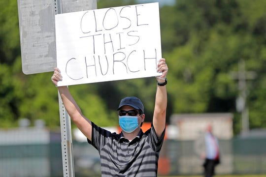 Protestor Trey Bennett holds a sign towards members of the Life Tabernacle Church waiting outside the East Baton Rouge Parish jail for Pastor Tony Spell to post bond in Baton Rouge, La., Tuesday, April 21, 2020.