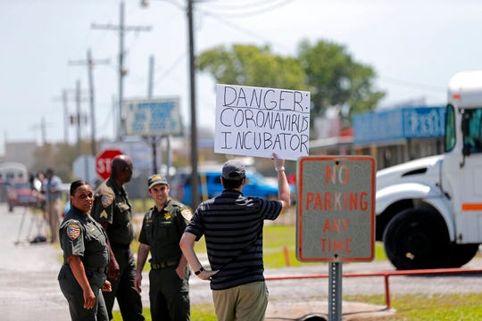 Protestor Trey Bennett holds a sign towards members of the Life Tabernacle Church as they leave the East Baton Rouge Parish jail after Pastor Tony Spell posted bond in Baton Rouge, La., Tuesday, April 21, 2020.