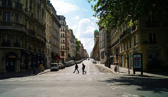 People cross a deserted street during nationwide confinement measures to counter the Covid-19, in Paris, Monday, April 27, 2020. France continues to be under an extended stay-at-home order until May 11 in an attempt to slow the spread of the COVID-19 pandemic.