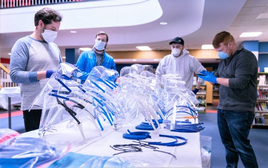 A team of Corning Inc. scientists assemble face shields made with 3-D printers for donation to local hospitals in the fight against the coronavirus.