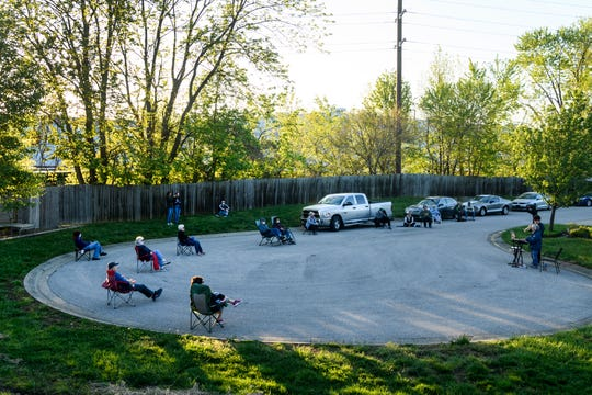 Judy Pereboom and her 16-year-old grandson Elliot Pereboom, far right, play music together in the cul-de-sac outside of Pereboom's home as neighbors watch while following social distancing guidelines in Evansville, Ind., Sunday evening, April 26, 2020.