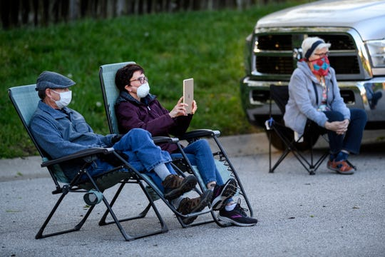 Doug and Linda Chambliss and other neighbors watch Judy Pereboom and her 16-year-old grandson Elliot Pereboom play music together in the cul-de-sac outside of Judy's home in Evansville, Ind., Sunday evening, April 26, 2020.