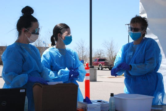 Heather Bell, Leigha Cortez and Leloni Williams, medical assistants for Banner Health, prepare to test patients for COVID-19 at Banner's testing site in Fort Collins. The drive-up testing site is one of two Banner opened in Fort Collins and Greeley today.