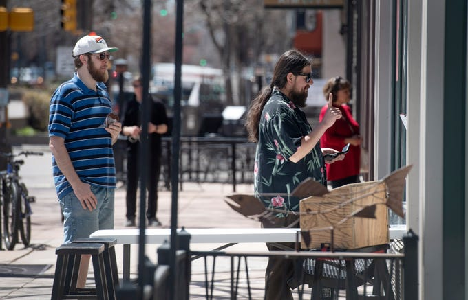 A man orders from Mary's Mountain Cookies during the first day of the 'safer-at-home' coronavirus guidelines in Old Town in Fort Collins, Colo. on Monday, April 27, 2020.
