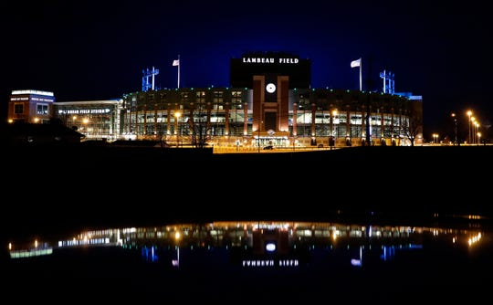 The bowl of Lambeau Field glows blue from the video boards, which thanked frontline workers during the coronavirus pandemic as part of the #LightItBlue campaign on April 9, 2020, in Green Bay, Wis.