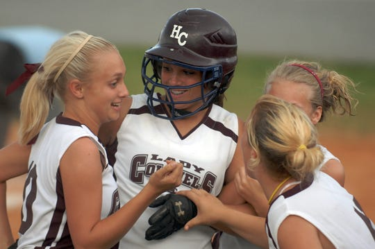 Henderson County's Katelyn McMillan, center, is congratulated by teammates after she hit her second straight home run during the 2009 Second Region Tournament semifinal against Hopkins County Central in Eddyville.