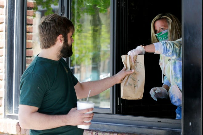 "Aaron Denham hands a customer their order through a window at DT Kirby's, Monday, April 27, 2020 in Lafayette. After closing due to the state's restrictions to restaurants in March, the Main Street restaurant reopened Monday with a modified ""fast food pop up"" menu."