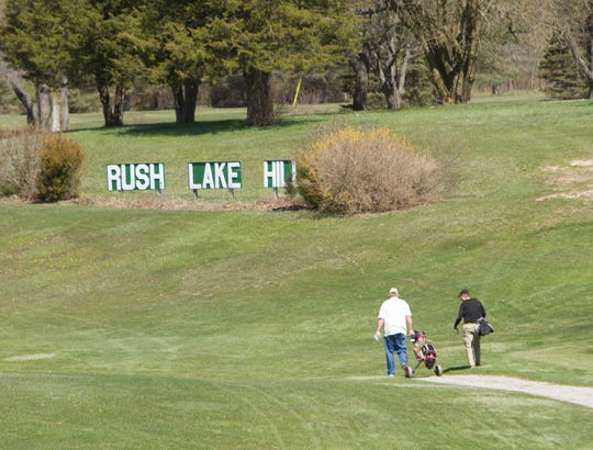 Golfers walk the course at Rush Lake Hills Golf Club Monday, April 27, 2020. Hamburg Township may buy the club, a lake and hundreds of acres of woodlands and wetlands.