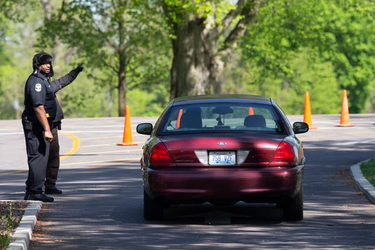 A car is directed to a COVID-19 testing site in Shawnee Park in Louisville on Monday.