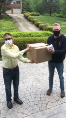 Dr. Muhammad Babar, left, presented a box of protective masks to David McKenzie, who's been scrambling to get protective gear for his small nursing home in Louisa, Kentucky.