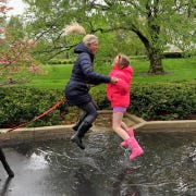 Kentucky first lady Britainy Beshear jumps in a rain puddle with her daughter, Lila.