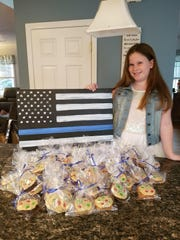 Caoimhe Assad with cookies she baked to raise funds. A nine-year-old Massachusetts girl donated St. Michael medals to all MIPD officers to help keep them safe.