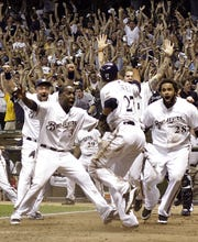 Carlos Gomez (27) is mobbed by teammates as he scored the winning for the Brewers in Game 5 of the National League division series against the Diamondbacks.