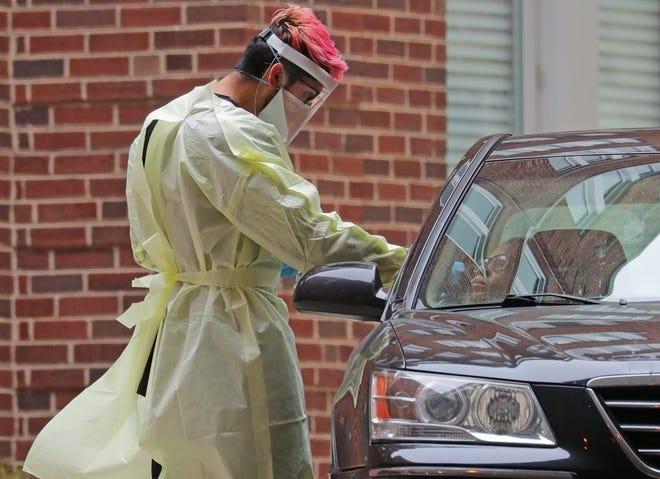 A health care professional administers a drive-through test for COVID-19 to a passenger in a vehicle at Ascension Southeast Wisconsin hospital Saint Joseph campus on West Chambers Street in Milwaukee on Monday. Ascension Wisconsin offers drive-through testing for the coronavirus at six sites in southeastern Wisconsin for people who have been pre-screened and approved.