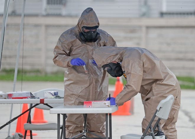 Wisconsin National Guard members Spec. Chris Faber, left, and Sgt. Kenneth Meyer, work together after administering a drive-through COVID-19 test in Milwaukee on April 27.