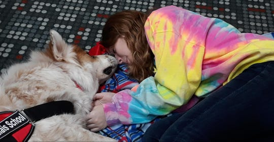 Calais School student, Madison, snuggles with Gideon during a counseling session at the Whippany school that uses dogs in its special education and counseling programs.