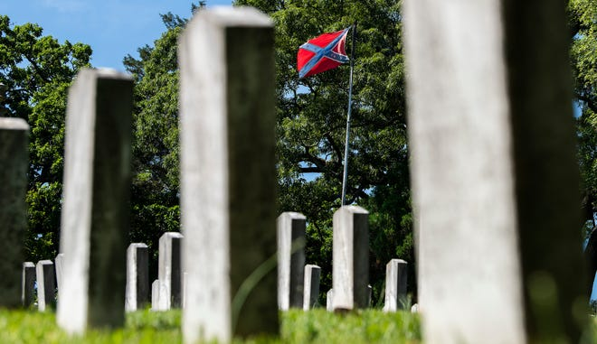 A confederate flag flies over grave markers of confederate soldiers in Oakwood Cemetery in Montgomery, Ala., on Confederate Memorial Day Monday April 27, 2020.
