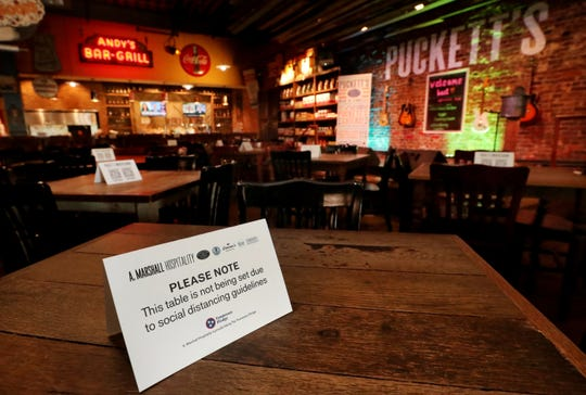 There are signs on tables at Puckett's Grocery & Restaurant in downtown Murfreesboro explaining why the tables are not currently being used. The restaurant reopened its dining areas on Monday, April 27, 2020, for the first time since being forced to close because of the coronavirus.
