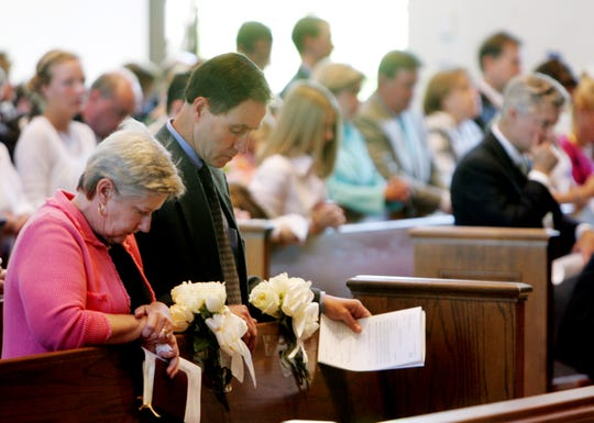 Mary and Ken Hall pray as they sit behind the flower-marked pew of church members Bill and Frankie Rutledge, who died in the flood, during a service at St. George's Episcopal Church on May 9, 2010. The Rutledges, who sat in the same pew every Sunday, were reported to be on their way to the church when the accident occurred.