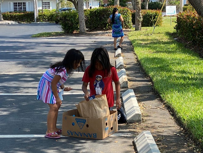 Children eagerly look into a food box recently distributed at Our Daily Bread Food Pantry mobile outreach on Marco Island, where 150 families were served.