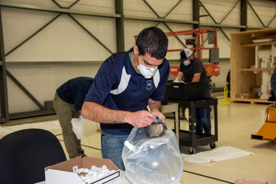 In The Spaceship Company facility in Mojave, California, engineer Mike Buttigieg cuts a hole in an oxygen hood that will be used by doctors to access COVID-19 patients.